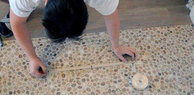Наносим разметку на полу, используя шаблон, и переносим её на потолок световым нивелиром